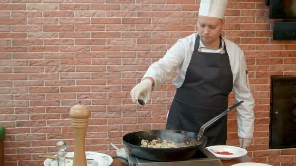 Kuchař, uvedení lžíce s kořením do pánve, designerské mořské plody