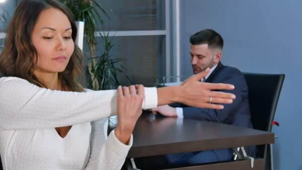 Portrait of a young woman stretching hands in office