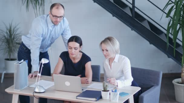 Startup business team on meeting in modern bright office interior brainstorming, working on laptop