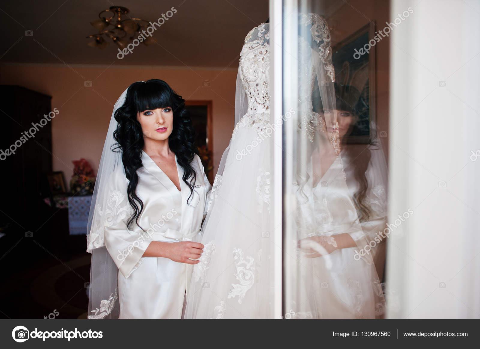 Junge niedliche Brünette Braut Blick auf ihr Brautkleid auf manneq ...