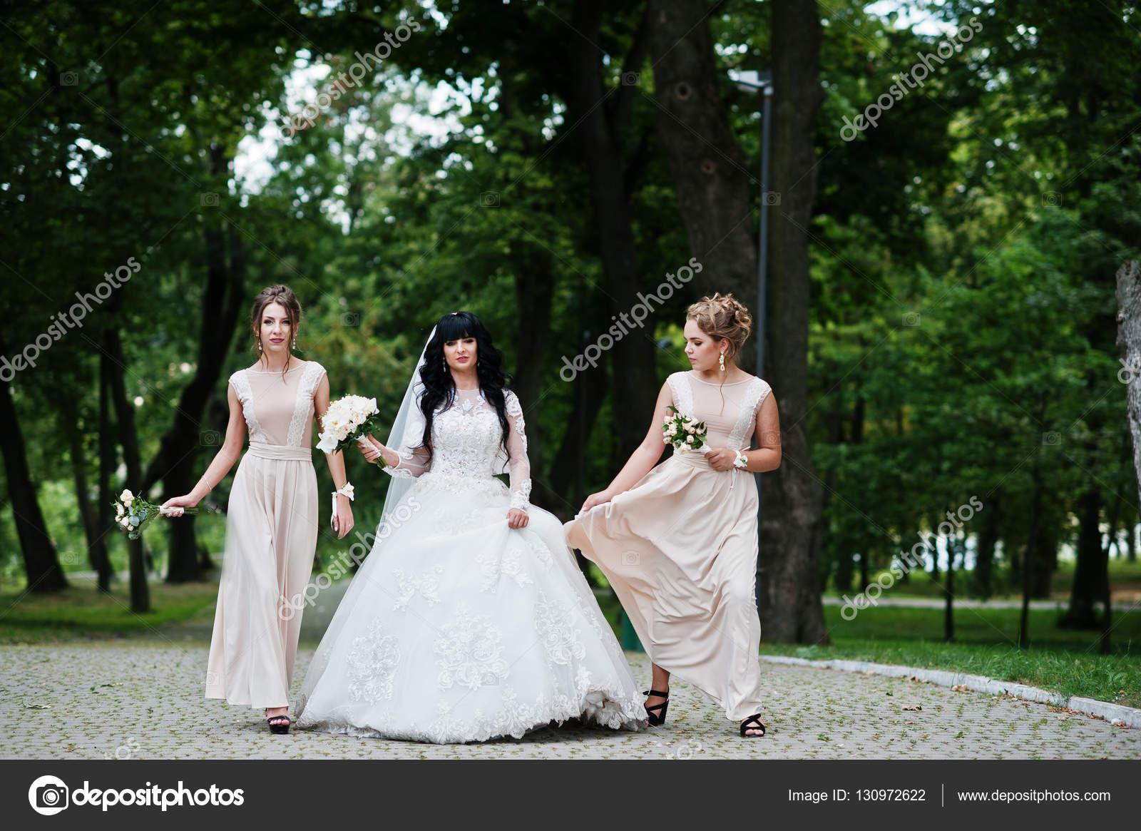 Schöne Braut mit Brautjungfern in Beige Kleid am Weg am Park mit ...