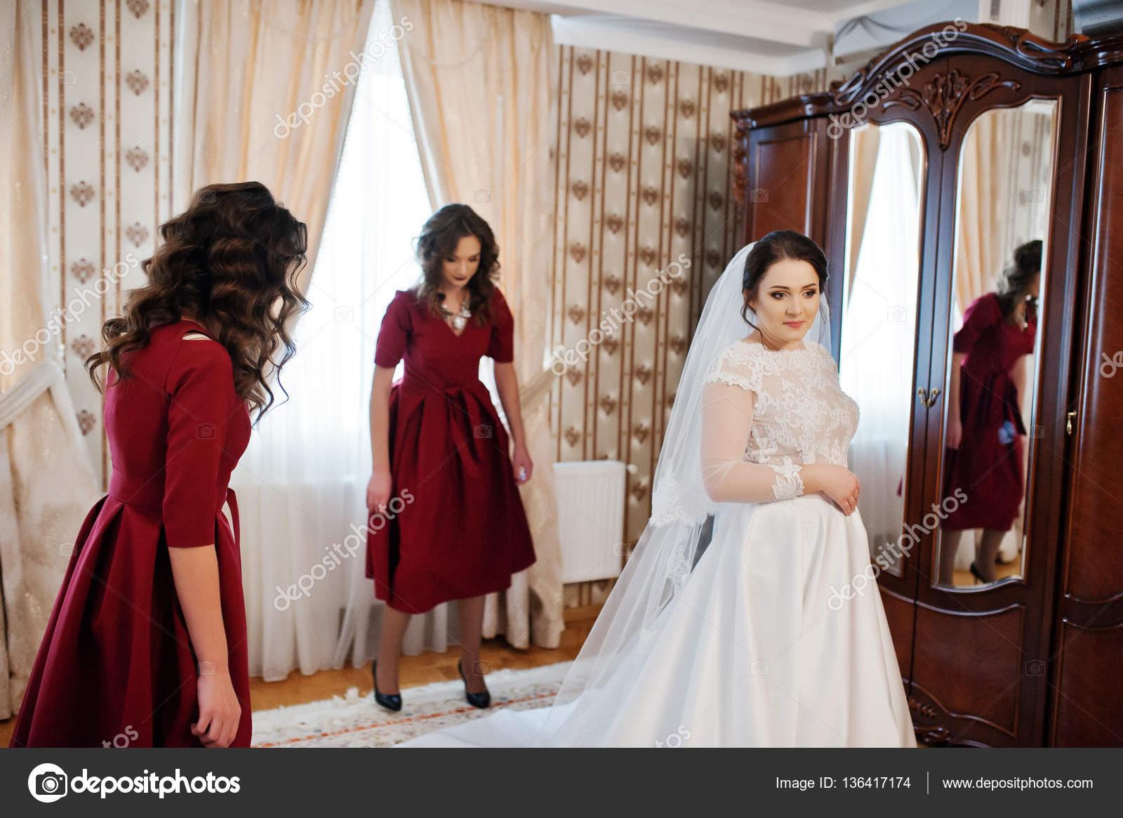 Zwei junge und wunderschöne Brautjungfern auf roten Kleid tragen ...