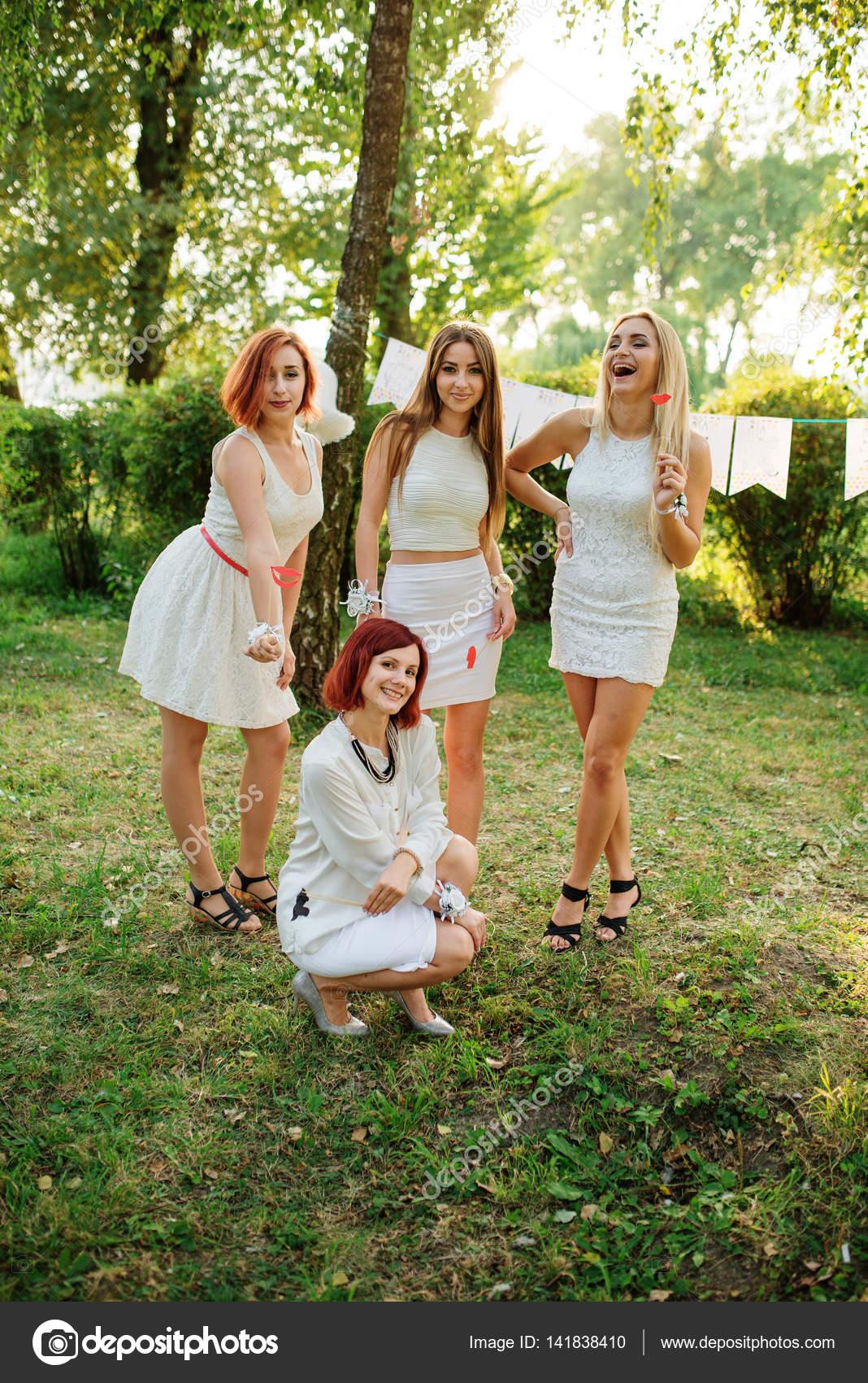 Mädchen tragen weiße Kleider, die Spaß am Junggesellinnenabschied ...