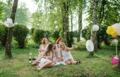 Five girls weared on white dress on hen party sitting outdoor an
