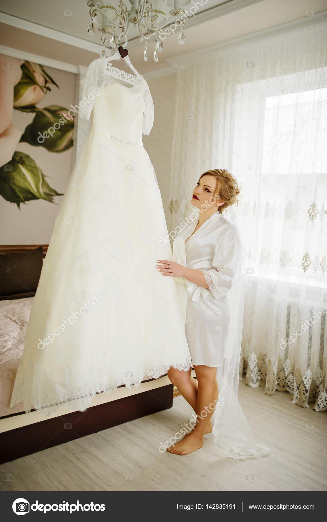 Blonde Braut im Brautkleid in ihrem Zimmer betrachten Bademantel ...