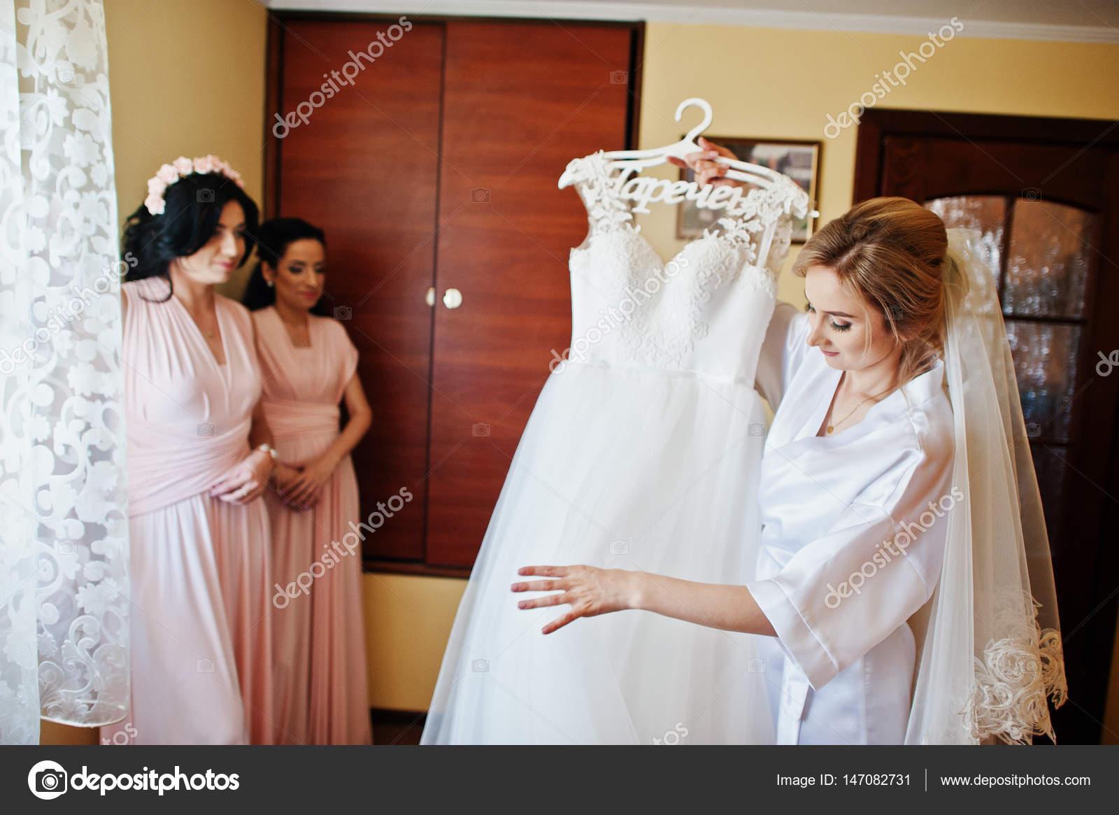Braut auf seidenes Gewand Blick auf ihr Brautkleid gegen bridesma ...