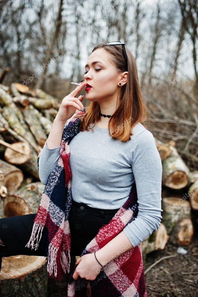 Young girl smoking cigarette outdoors background wooden
