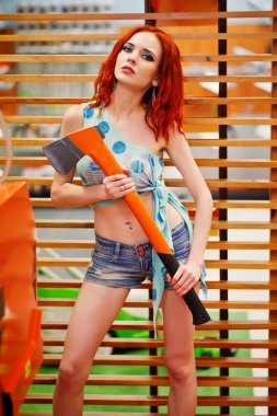 Red haired slim model posed with axe at store or household shop
