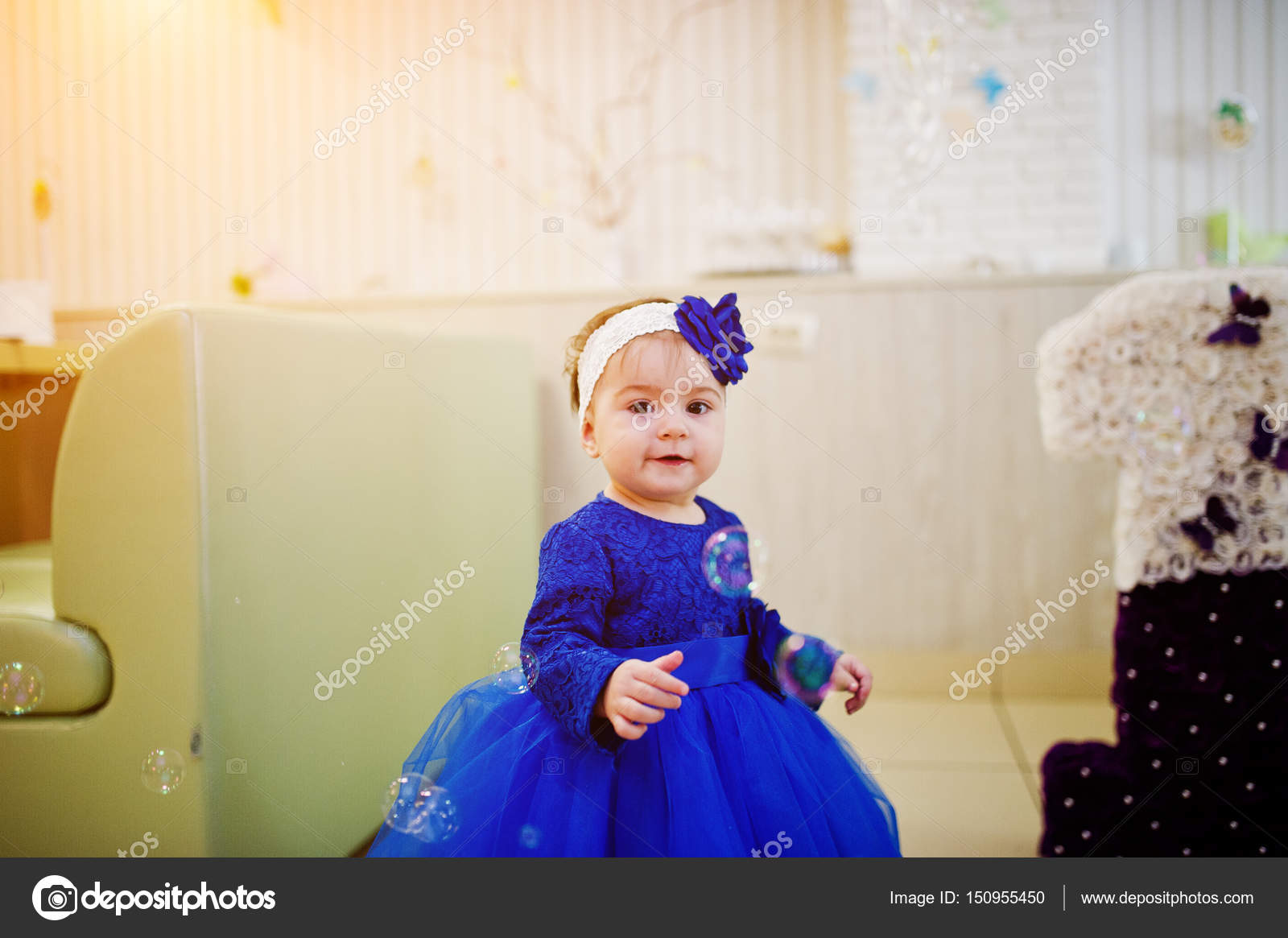 62a069a66 Cute little baby girl at blue dress play with soap bubbles. 1 ye ...