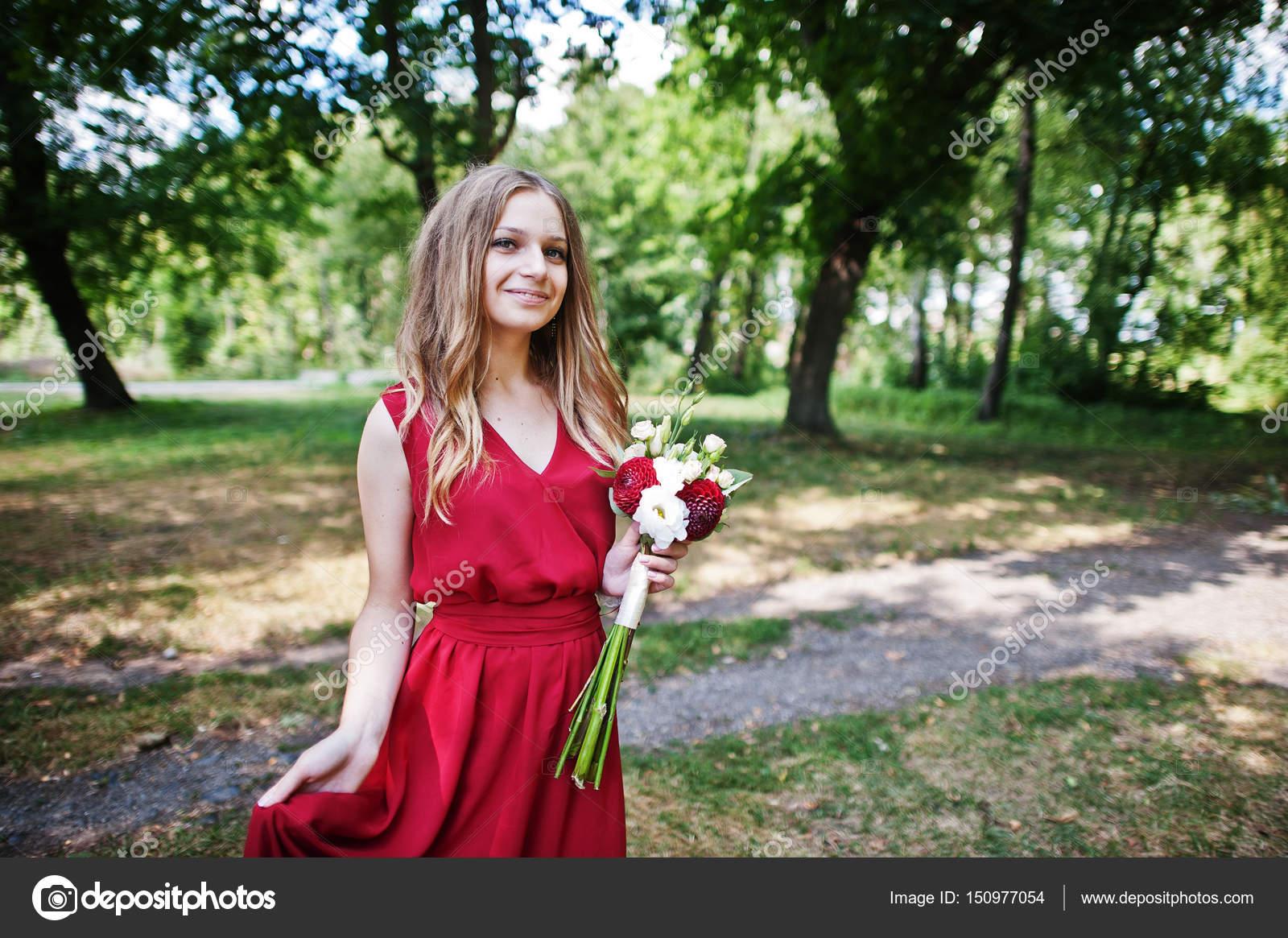 ffc8c5e7468b Damigella d onore ragazza carina al vestito rosso con bouquet da sposa a  portata di mano– immagine stock