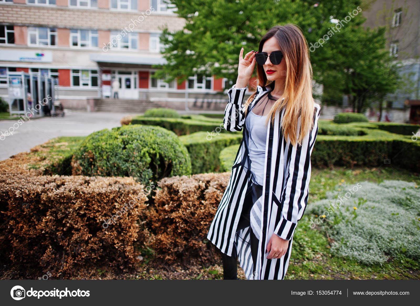 276cd4a7d9 Divatos nő meg fekete-fehér csíkos öltöny zakó, bőr nadrág és napszemüveg  jelentő bokrok utca ellen. Divat lány fogalmának — Fotó szerzőtől ...