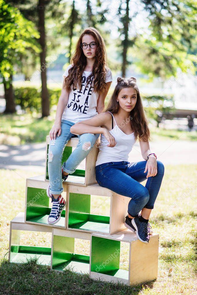 Zwei geile junge Girls sitzen auf Holzkisten im Park auf