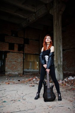 Red haired punk girl wear on black with bass guitar at abadoned