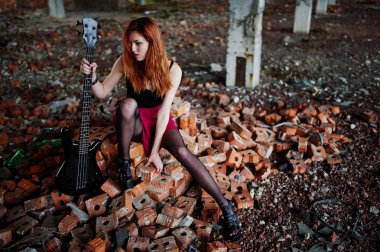Red haired punk girl wear on black and red skirt, with bass guit