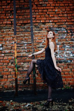 Red haired punk girl wear on black dress at the roof against bri