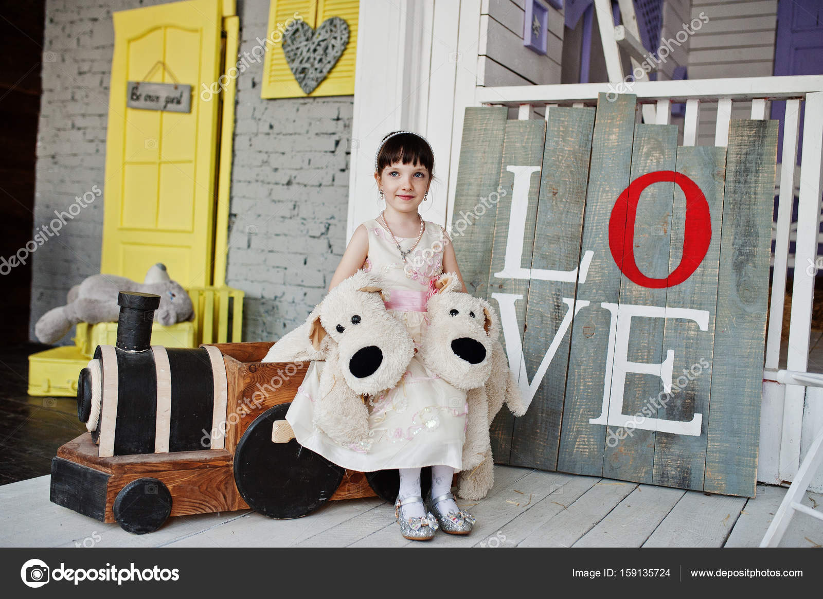 79d1f92a645bd Portrait of a cute girl in a dress sitting on wooden small train — Stock  Photo