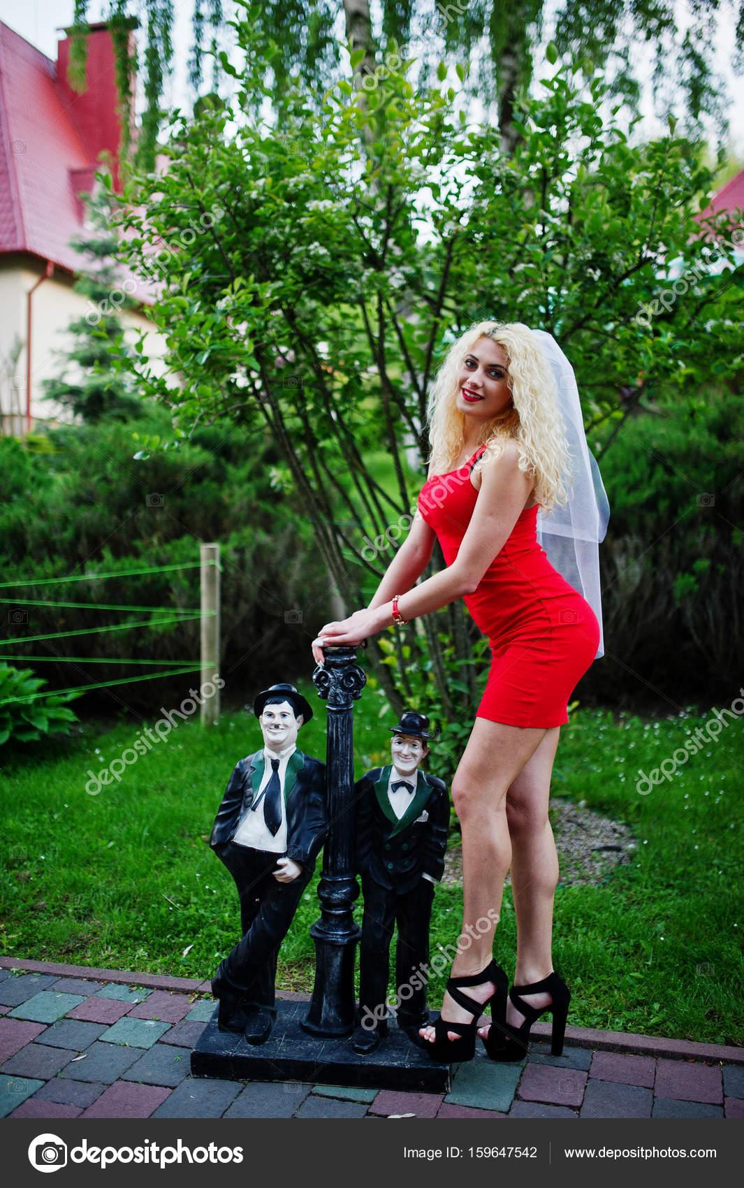 Wunderschöne Braut tragen rote Kleid und Schleier posiert außerhalb ...