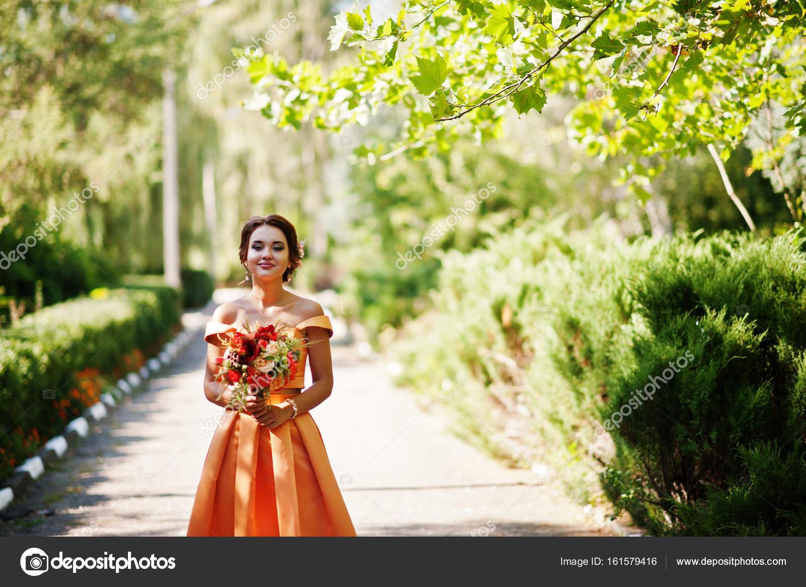 Atractiva dama de honor vestido naranja con ramo de novia — Foto de ...