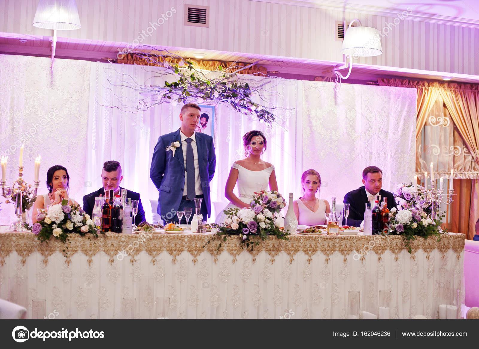 Hermosa pareja de pie en su mesa con la Dama de honor — Fotos de ...