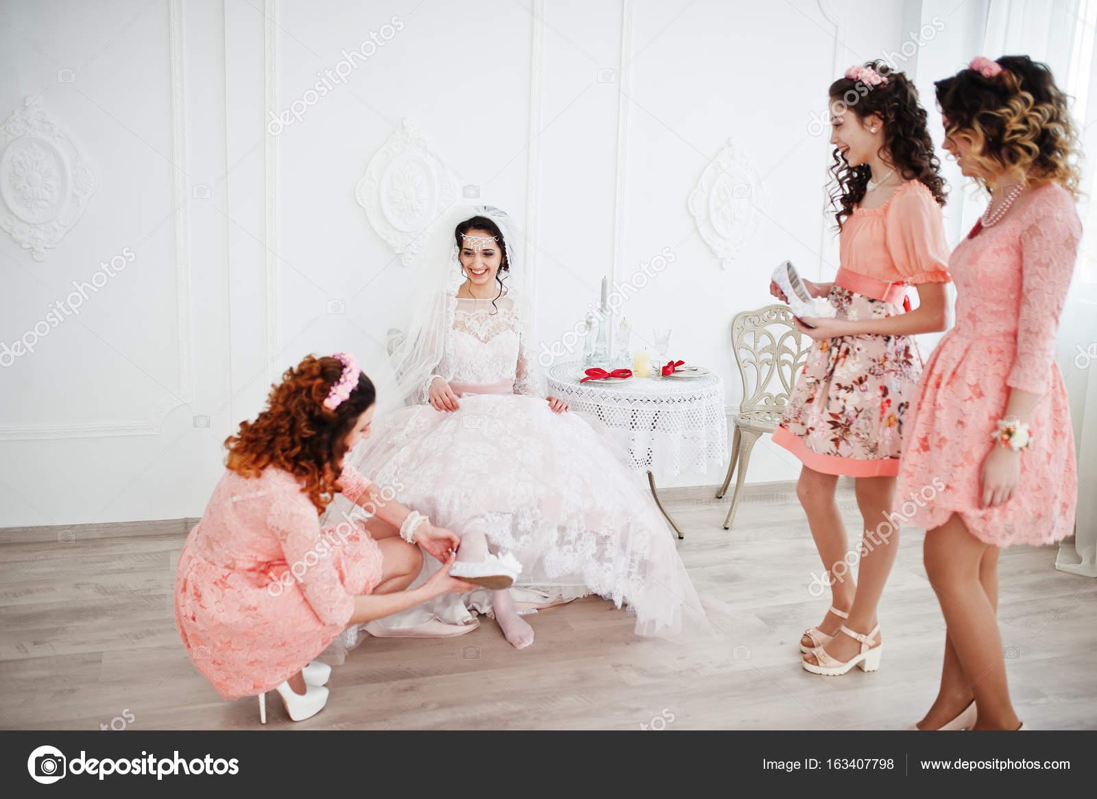 3f84b4289c88 Aiutare la sposa a mettere le sue scarpe da sposa e ottenere pronto per il  suo matrimonio damigelle — Foto di ...