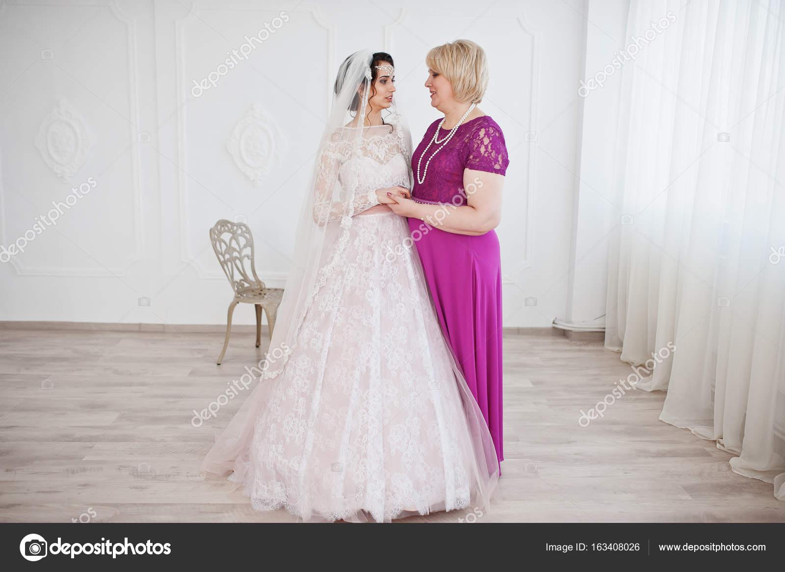 Schöne Braut im Hochzeitskleid posiert mit ihrer Mutter in lila lo ...