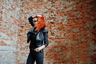Red haired stylish girl in sunglasses wear in black, against aba