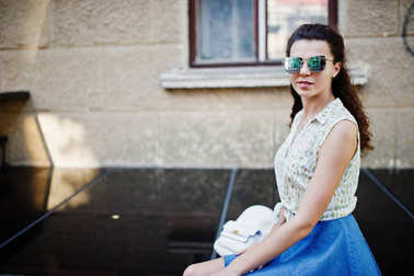 Curly stylish girl wear on blue jeans skirt, blouse and sunglass