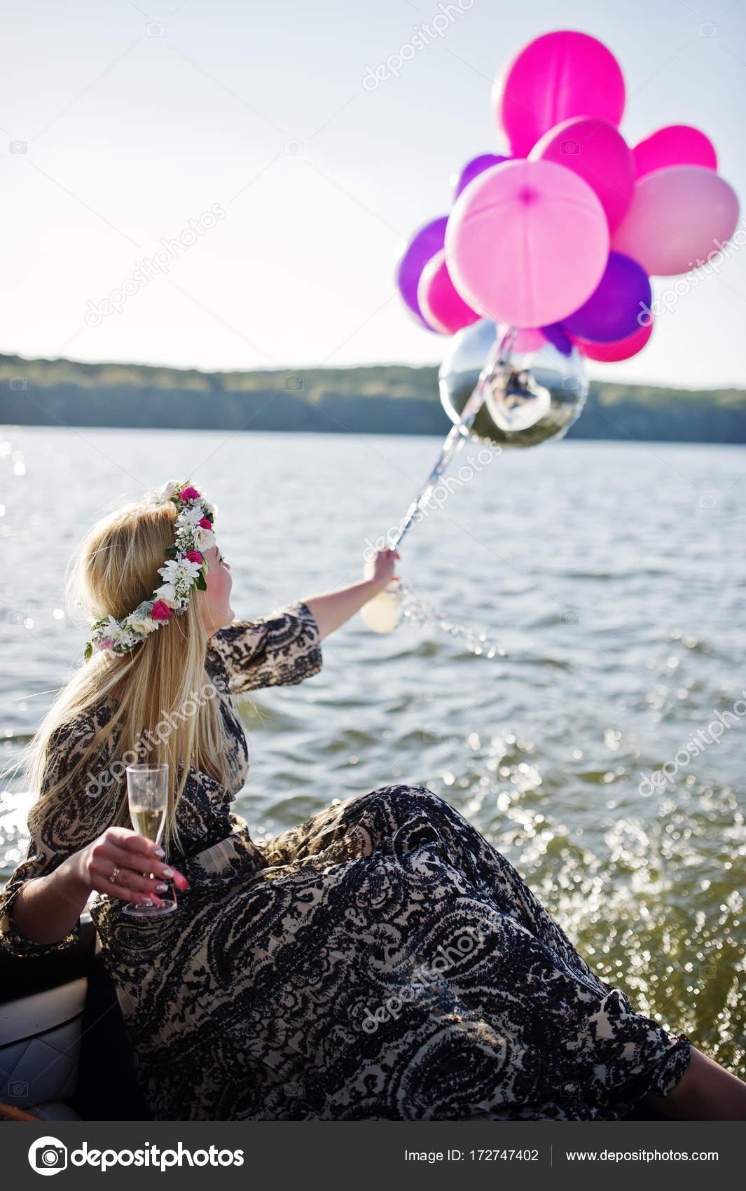 Blonde Mädchen in Kranz sitzen auf Yacht am Polterabend mit champag ...