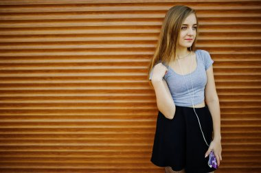 Young blonde girl in black skirt listening music from headphones