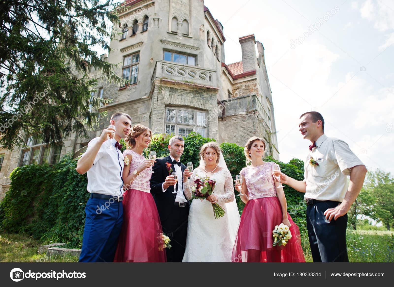 0d7f0e3d13f9 Sposi e damigelle d onore con groomsmen bevendo champagne accanto al  Castello — Foto di ASphoto777