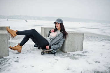 Stylish brunette girl in gray cap, casual street style with skat