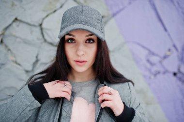Stylish brunette girl in gray cap, casual street style on winter