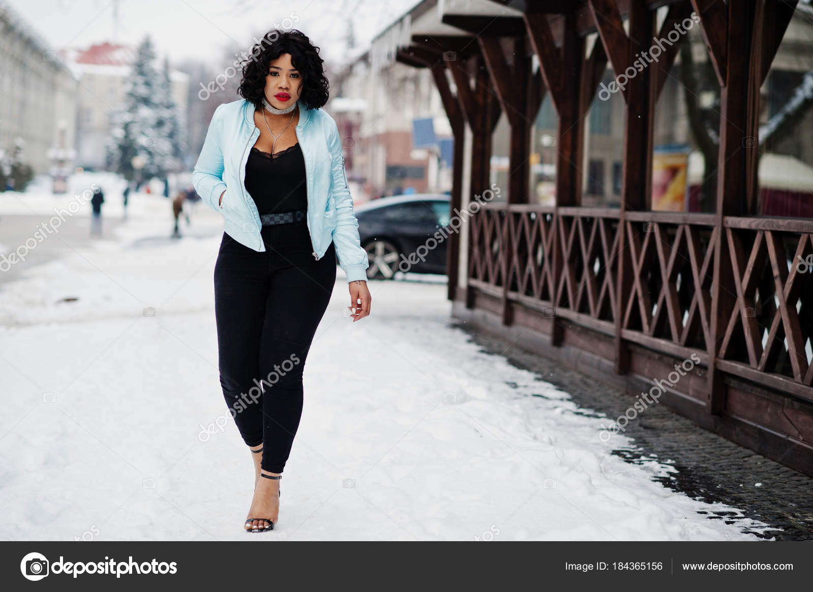 Stylish african american plus size model against wooden cafe ...