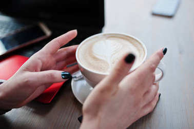 Close up hands of girl with cup of cappuccino background red lap