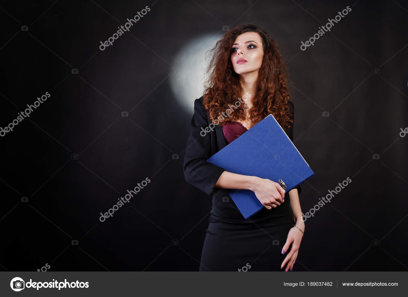 Brunette fille aux cheveux bouclée au bureau noir veste avec jupe