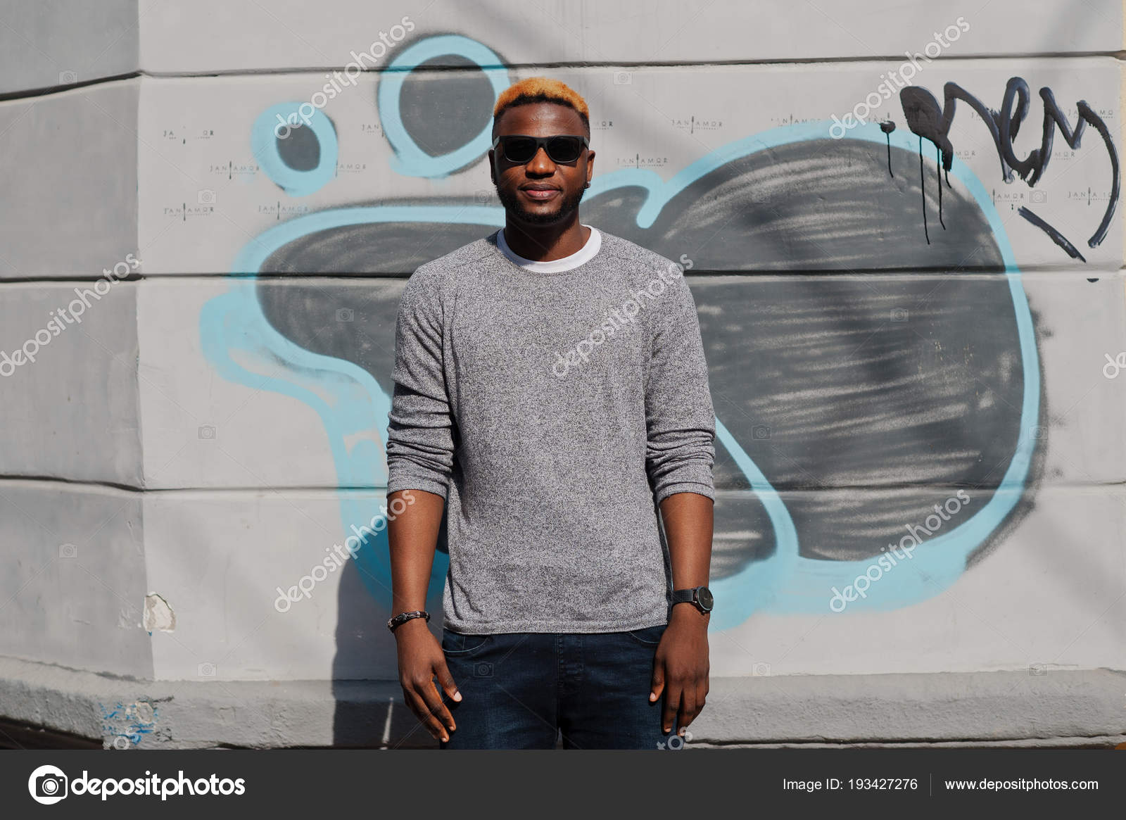 dbce041013a Stylish african american boy on gray sweater and black sunglasses posed at  street. Fashionable black guy against graffity wall. — Photo by ASphoto777