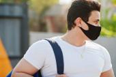 Portré sport arab férfi fekete orvosi arc maszk hátizsák pózol sárga háromszög alatt koronavírus karantén.