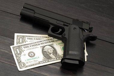Black gun on banknotes. Concept of armed criminal offenses