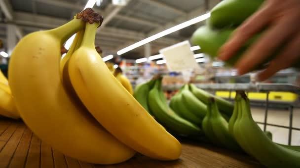 Kupující vybírá banány na čítač supermarketu