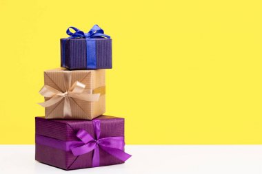 Vertical boxes with gifts in multi-colored paper for different holidays and events. Copy space, yellow background.