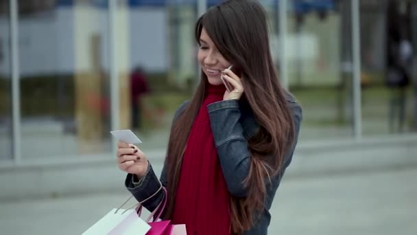 glückliche Frau, die nach dem Einkaufen auf der Straße telefoniert. Porträt einer schönen lächelnden Frau mit Kreditkarte in der Hand, die im Freien telefoniert. Mädchen mit Smartphone.