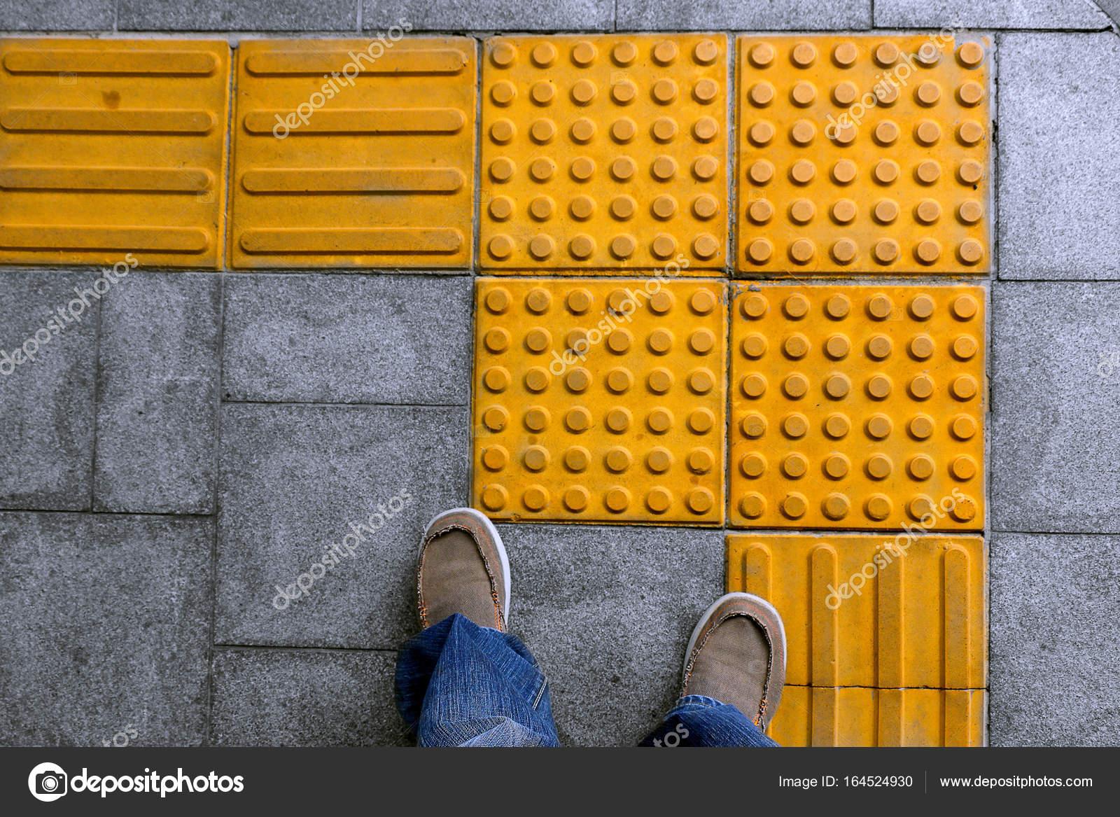Scarpe sul blocco tattile pavimentazione per non vedenti handicap