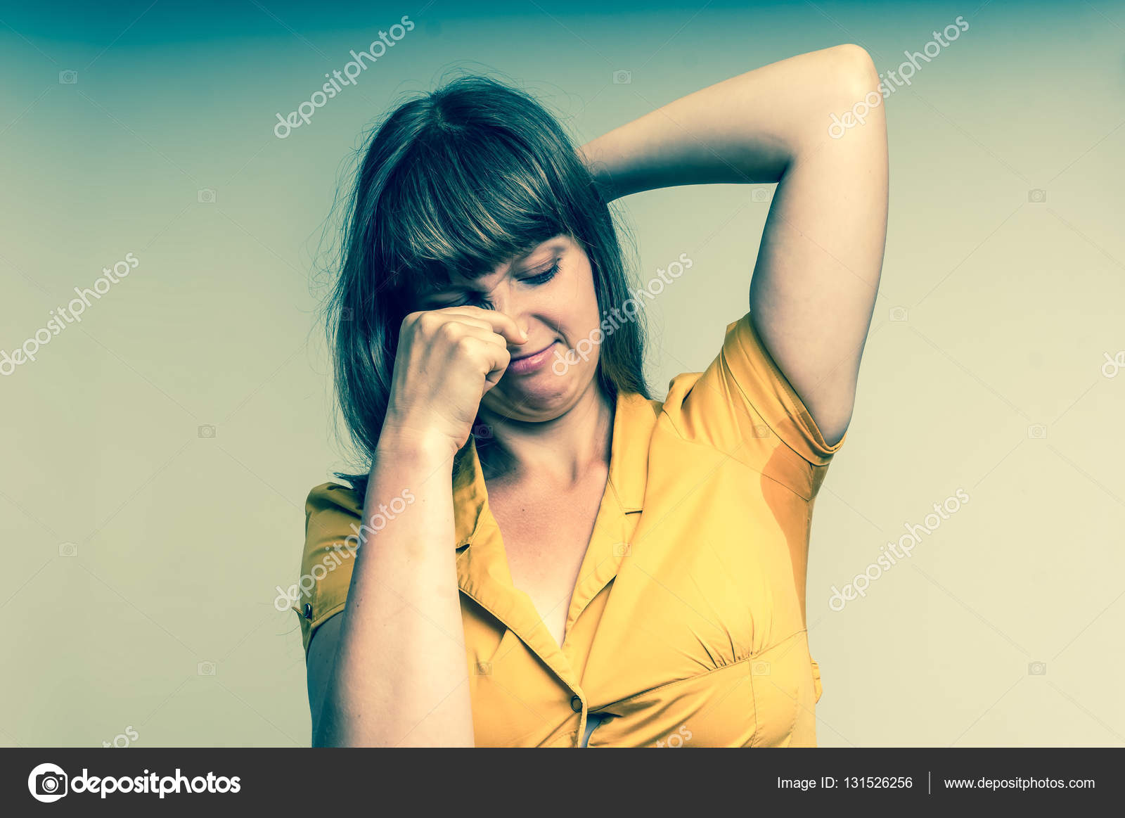 woman with sweating under armpit in yellow dress stock photo