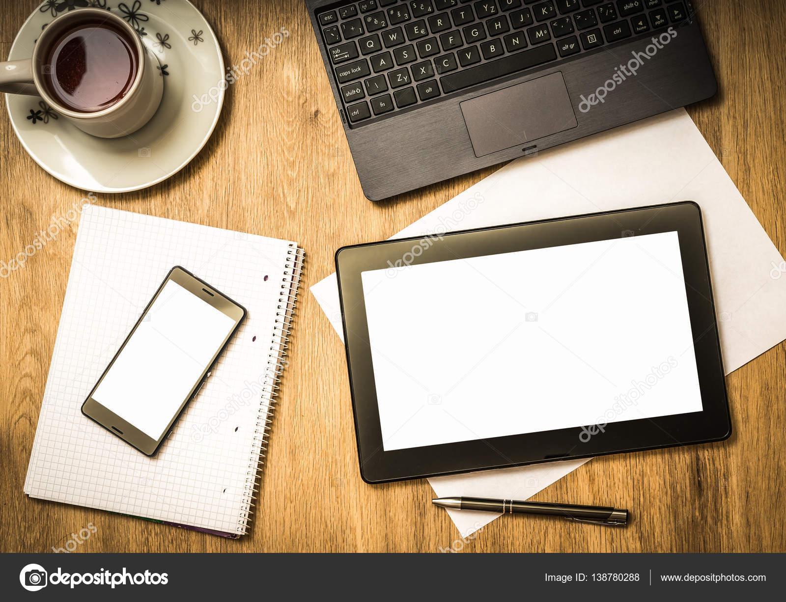 Tablette numérique avec écran blanc sur une table en bois au