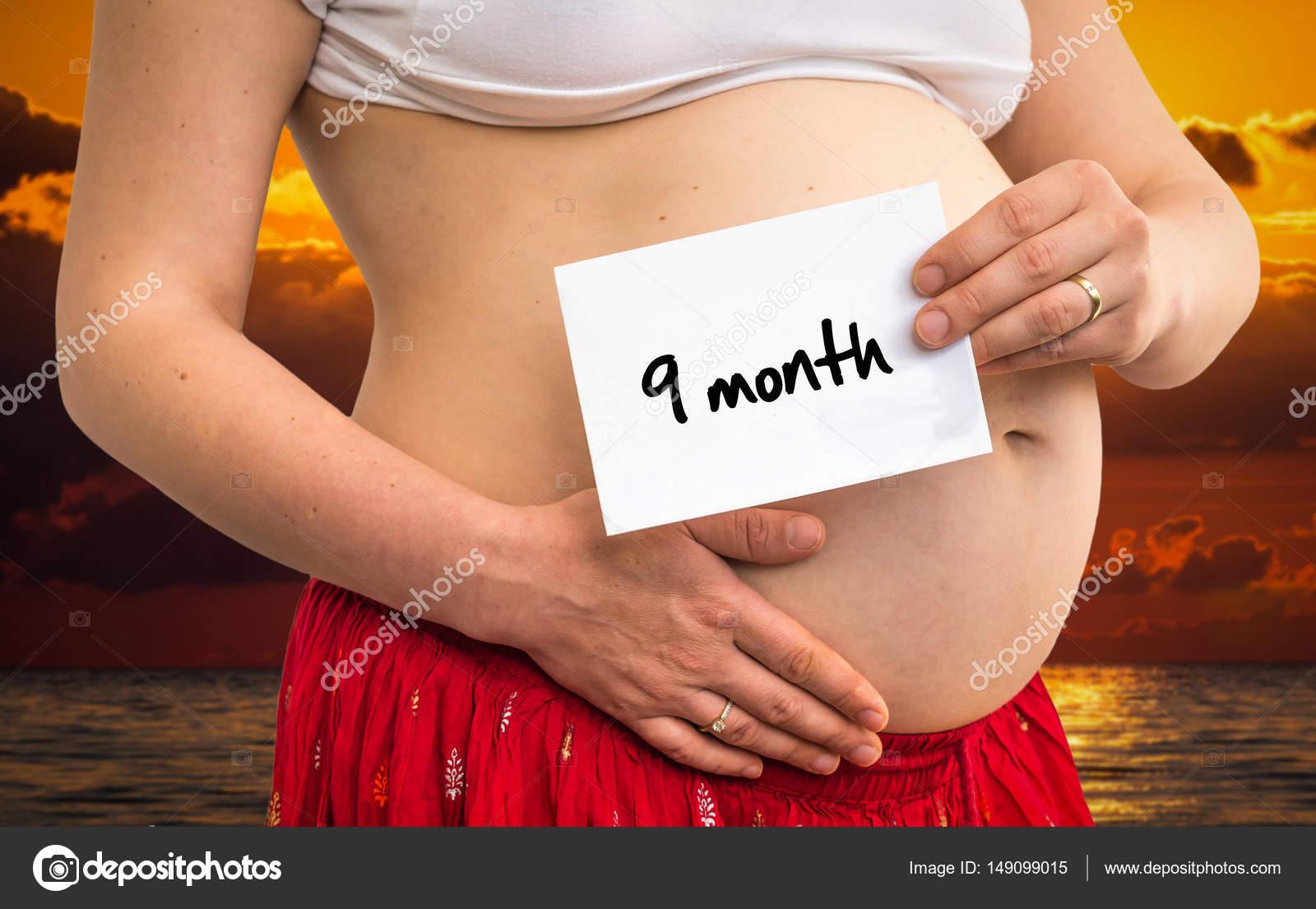 e3e0a21e1 Mujer embarazada con papel con la inscripción  9 meses — Foto de Stock