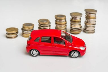 Toy car and coin stack - insurance, loan and buying car