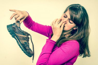 Woman holding dirty stinky shoes - retro style
