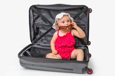 Happy little kid inside suitcase isolated on white