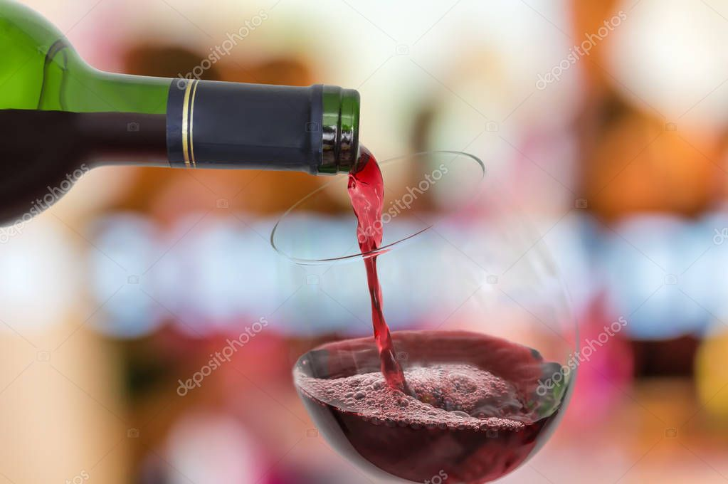 Red wine pouring into a wine glass - celebration concept