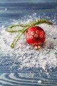 červené vánoční ozdoby na smrkové větve se sněhem